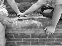 Old School Gaming. A mother and child playing tic tac toe on the sidewalk Royalty Free Stock Images