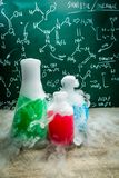 Old school laboratory with beakers chemical formula. On old wooden table Stock Photo
