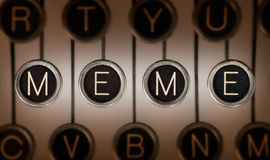Old School Meme. Close up of old typewriter keyboard with scratched chrome keys that spell out MEME. Lighting and focus are centered on MEME Royalty Free Stock Image