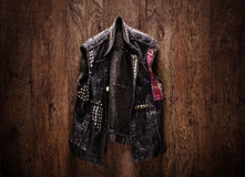 Old-school punk-rock leather jacket. Hanging on a wooden background Stock Image