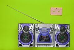 Old school retro tape recorder and audio cassette on a green background. Obsolete technologies. Trend of minimalism. Top view. Copy space Stock Photos