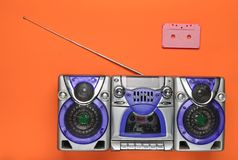 Old school retro tape recorder and audio cassette on an orange background. Obsolete technologies. Trend of minimalism. Top view. Stock Photos