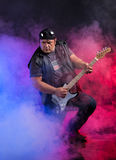 Old school rock musician is playing guitar. Old school rock musician is playing electrical guitar. Shot in a studio Stock Photo