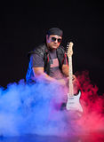Old school rock musician is playing guitar. Old school rock musician is playing electrical guitar. Shot in a studio Royalty Free Stock Photography
