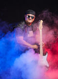 Old school rock musician is playing guitar. Old school rock musician is playing electrical guitar. Shot in a studio Stock Image