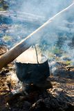 Old school way of making tea outdoor. Steam and smoke all around. black cauldron hang on the log above the fire place. wonderful taste of summer and hike in stock image