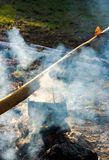Old school way of making tea outdoor. Steam and smoke all around. black cauldron hang on the log above the fire place. wonderful taste of summer and hike in royalty free stock images