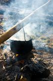 Old school way of making tea outdoor. Steam and smoke all around. black cauldron hang on the log above the fire place. wonderful taste of summer and hike in stock photography