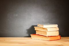 Old schoolbooks lying on a wooden school desk in front of a black chalkboard. Education concept - the desk in the auditorium.  stock photography