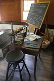 Old schoolroom. A chalkboard and desk in an old schoolroom Royalty Free Stock Photos