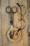 Old scissors, glasses and hank of packthread over wooden texture Stock Images