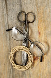 Old scissors, glasses and hank of packthread on wooden backgroun Royalty Free Stock Images
