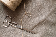 Old scissors and skein jute twine on a burlap, rustic Stock Photography