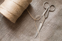 Old scissors and skein jute twine on a burlap, rustic Royalty Free Stock Photography