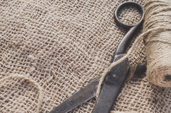 Old scissors and skein jute twine on a burlap, selective focus, rustic style. Stock Images