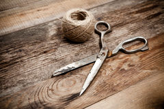 Old scissors and skein jute on wooden table Stock Photography