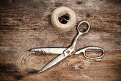 Old scissors and skein jute on wooden table Royalty Free Stock Image