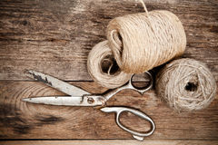 Old scissors and skein jute on wooden table Royalty Free Stock Photography