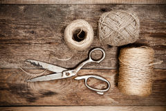 Old scissors and skein jute on wooden table Royalty Free Stock Images