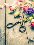 Old scissors with summer flowers on blue wooden table Stock Images
