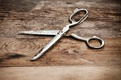 Old scissors on the wooden table Stock Image