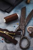 Old scissors, zipper for clothes and other tools for sewing and minor repairs. Close-up stock photography