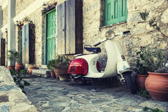 Old scooter parked by the wall in the empty street of Karpathos, Royalty Free Stock Image