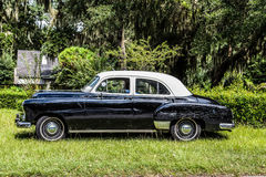Old Scratched Black Car. An old black and white car scratched and dented in grass royalty free stock photo