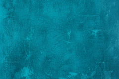 Old scratched and chapped painted blue wall. Abstract textured turquoise background. Empty template stock photography