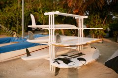 Old scratched and damaged surfboards on a rack stand for repair on the beach. Old scratched and damaged surfboards on a rack stand for repair Royalty Free Stock Photos