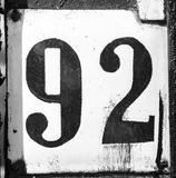 Old scratched metal plate with the number ninety-two. Close up Stock Image