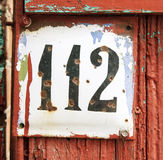Old scratched metal plate with the number one hundred twelve. Close up Royalty Free Stock Images