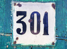 Old scratched metal plate with the number three hundred one. Close up Stock Photo