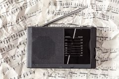Old radio receiver and music notes. Old scratched radio receiver on the crumpled notes background Stock Images