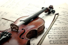 Old scratched violin with sheet music Stock Images