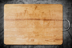 Old scratched wooden cutting board, on dark concrete texture Stock Images