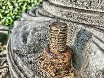 Old screw. One small detail of a column in a park Royalty Free Stock Photos