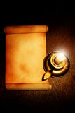 Old scroll and candle. On wooden table Royalty Free Stock Image
