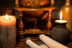 Old scroll with a globe and candles, concept adventure and trave Stock Image
