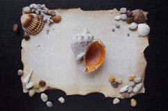 Old scroll of parchment with sea pebbles and Stock Photo