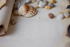 Old scroll of parchment with sea pebbles and Stock Image