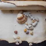 Old scroll of parchment with sea pebbles and Royalty Free Stock Photography