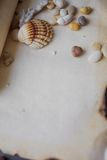 Old scroll of parchment with sea pebbles and Stock Photography