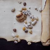 Old scroll of parchment with sea pebbles and Royalty Free Stock Images