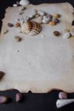 Old scroll of parchment with sea pebbles and Stock Images