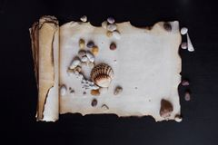 Old scroll of parchment with sea pebbles and Royalty Free Stock Photos