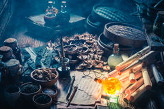 Old scrolls and recipe in vintage alchemist laboratory. Concept image Royalty Free Stock Photo