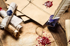 Old scrolls, sealing wax, old envelope and blue ink. On wooden table royalty free stock image