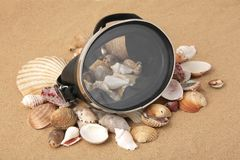 Old scuba mask and seashells. A closeup of a vintage scuba diving mask, placed atop seashells of various sizes on the beach Stock Photography