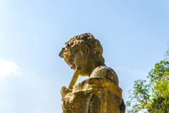 Old sculpture on the pedestal, beautifully preserved old artisti Royalty Free Stock Photo